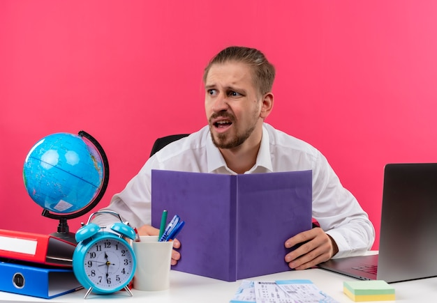 Przystojny biznesmen w białej koszuli z globu gospodarstwa notebooka patrząc na bok zdezorientowany siedzący przy stole w biurze na różowym tle