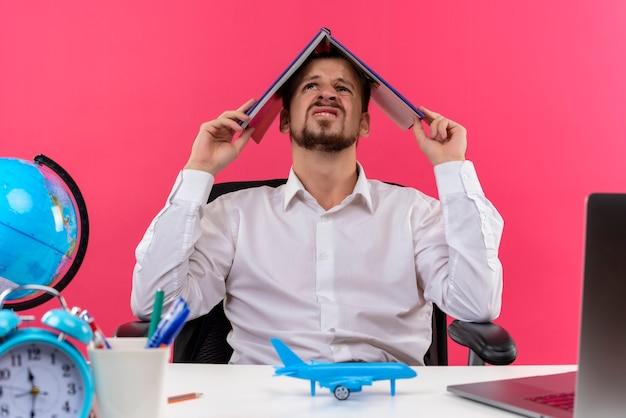 Przystojny biznesmen w białej koszuli z globu trzymając notebook nad głową, patrząc zdezorientowany, siedząc przy stole w biurze na różowym tle