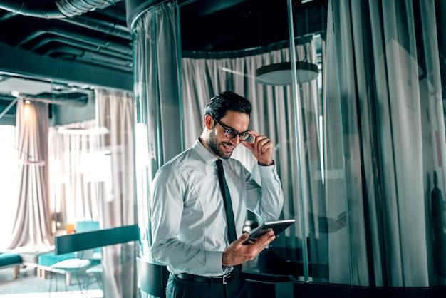 Przystojny biznesmen w biurze patrząc na tablet.