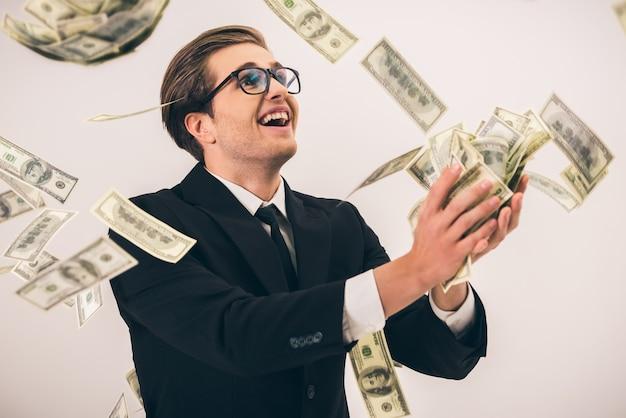 Przystojny biznesmen w garniturze i okularach łapie gotówkę.