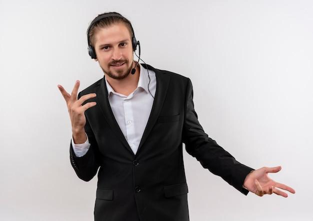 Przystojny biznesmen w garniturze i słuchawkach z mikrofonem patrząc na kamery z uśmiechem na twarzy gestykuluje rękami stojącymi na białym tle