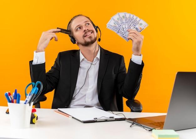 Przystojny biznesmen w garniturze i słuchawkach z mikrofonem trzymającym poduszkę i kartę kredytową o marzycielskim wyglądzie siedzi przy stole w biurze na pomarańczowym tle