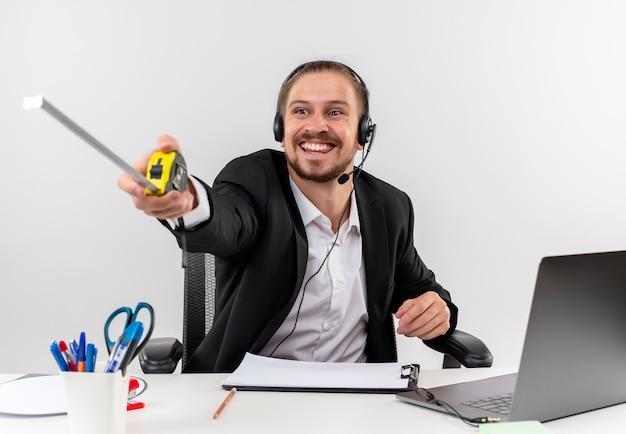Przystojny biznesmen w garniturze i słuchawkach z mikrofonem wskazującym taśmą mierniczą na bok z uśmiechem na twarzy siedzącej przy stole w biurze na białym tle