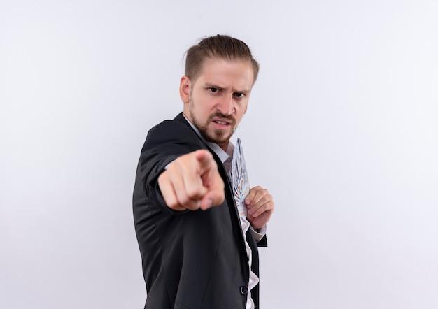 Przystojny biznesmen w garniturze trzymając gotówkę, wskazując palcem wskazującym na aparat z gniewną twarzą stojącą na białym tle