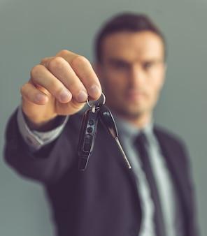 Przystojny biznesmen w klasycznym garniturze trzyma kluczyki do samochodu