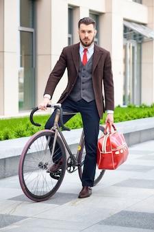 Przystojny biznesmen w kurtce z czerwoną torbą siedzi na swoim rowerze na ulicach miasta. pojęcie nowoczesnego stylu życia młodych mężczyzn