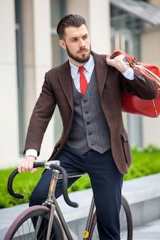 Przystojny biznesmen w kurtce z czerwoną torbą siedzi na swoim rowerze na ulicach miasta.
