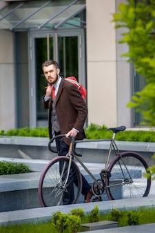 Przystojny biznesmen w kurtkę i czerwoną torbę i jego rower na ulicach miasta.