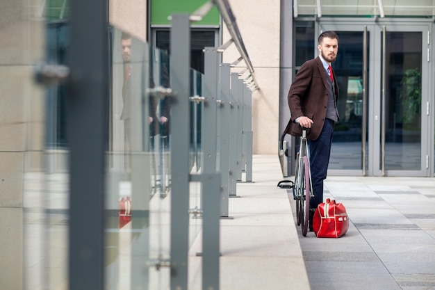 Przystojny biznesmen w marynarce i czerwonym krawacie i jego roweru na ulicach miasta. obok leży czerwona torba. pojęcie nowoczesnego stylu życia młodych mężczyzn