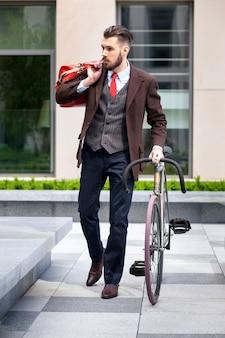 Przystojny biznesmen w marynarce i czerwonym krawacie i jego roweru na ulicach miasta. pojęcie nowoczesnego stylu życia młodych mężczyzn