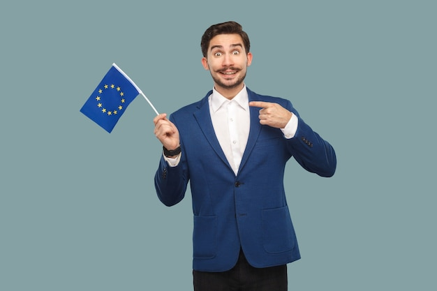 Przystojny biznesmen w niebieskiej marynarce i białej koszuli, trzymając i wskazując palcem na flagę unii europejskiej i patrząc na kamery z toothy uśmiechem. kryty, studio strzał na białym tle na jasnoniebieskim tle.