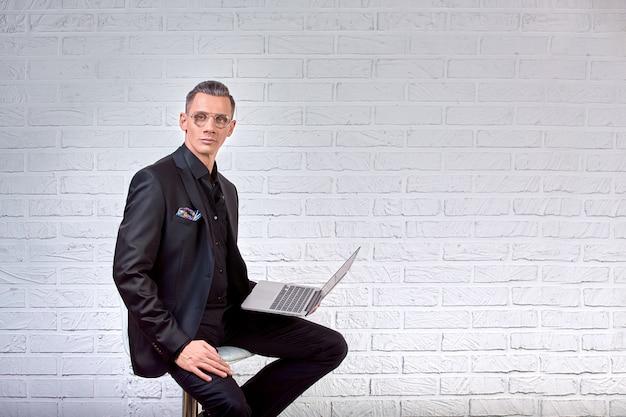Przystojny biznesmen w okularach i garnitur, trzymając laptop w ręce i coś pisze. widok z boku. na białej cegle