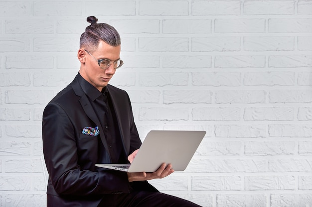 Przystojny biznesmen w okularach i garniturze trzymając laptopa w rękach i coś pisze.