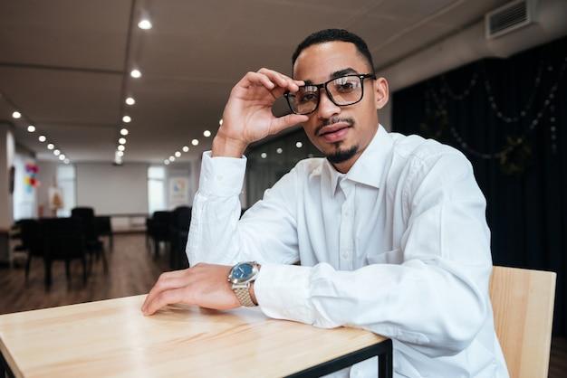 Przystojny biznesmen w okularach siedzący przy stole i patrzący z przodu