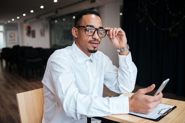 Przystojny biznesmen w okularach siedzący przy stole rozmawiający przez telefon