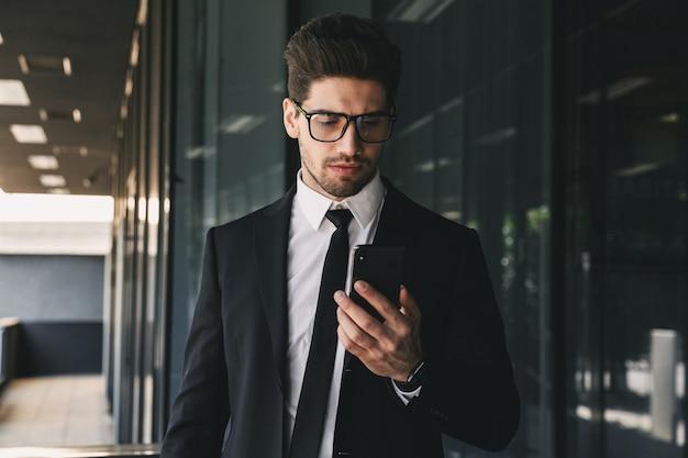 Przystojny biznesmen w pobliżu centrum biznesowego za pomocą telefonu komórkowego.