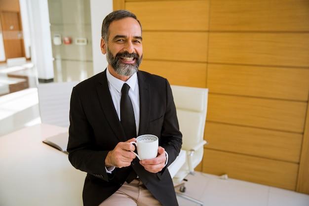 Przystojny biznesmen w średnim wieku, trzymając kubek kawy lub w biurze