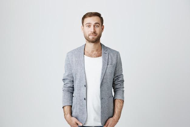 Przystojny biznesmen w szarej kurtce szuka aparatu