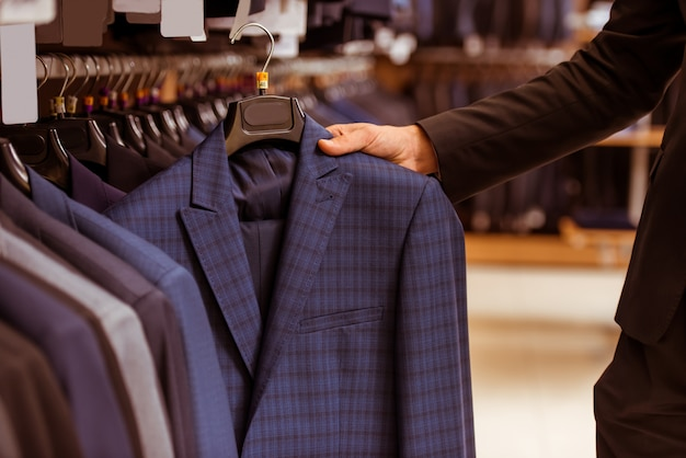 Przystojny biznesmen wybiera klasycznego kostium.