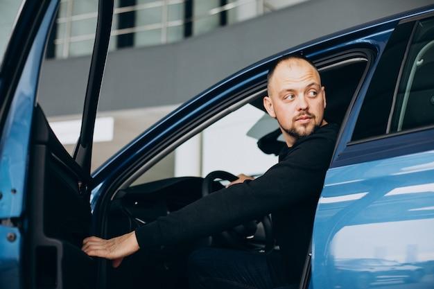 Przystojny biznesmen wybiera samochód w salonie samochodowym