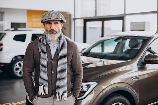 Przystojny biznesmen wybierający samochód w salonie samochodowym