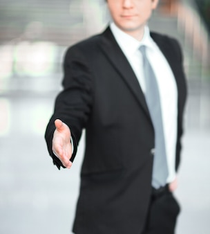 Przystojny biznesmen wyciągając rękę do uścisku dłoni. koncepcja partnerstwa
