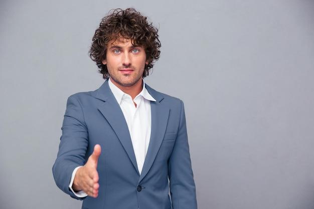 Przystojny biznesmen wyciąganie ręki do uścisku dłoni na szarej ścianie