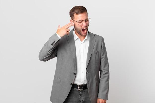 Przystojny biznesmen wyglądający na niezadowolonego i zestresowanego, gest samobójczy robiący znak pistoletu