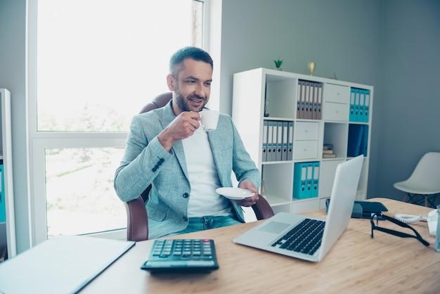 Przystojny biznesmen z niebieską kurtką pracujący w biurze