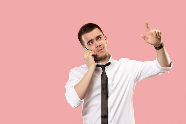 Przystojny biznesmen z telefonem komórkowym. młody biznesmen stojący na białym tle na tle różowego studia.