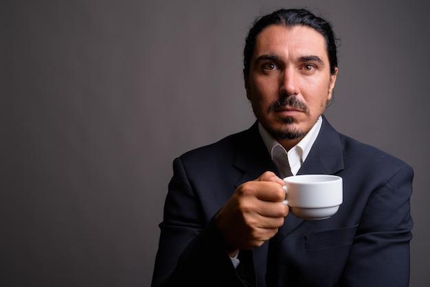 Przystojny biznesmen z wąsem na sobie garnitur przeciw szarej ścianie