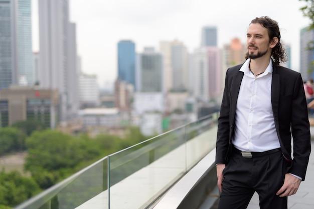 Przystojny biznesmen z widokiem na miasto w bangkoku w tajlandii
