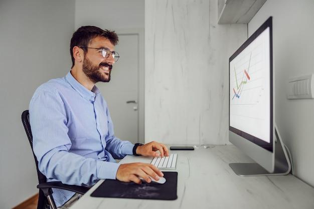 Przystojny biznesmen zadowolony siedzi w swoim biurze i pracuje nad ważnym projektem.