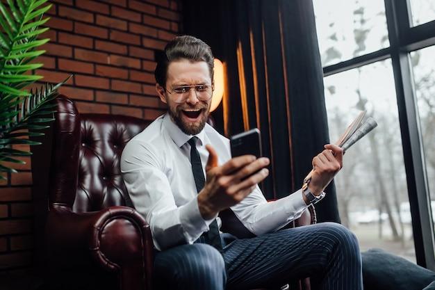 Przystojny biznesmen ze szczerymi emocjami trzymając smartfon i gazetę siedząc na fotelu.