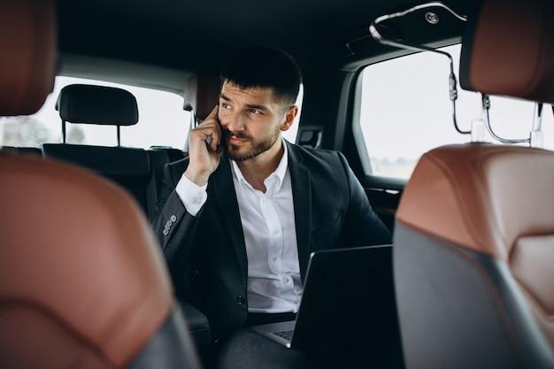 Przystojny biznesowy mężczyzna pracuje na komputerze w samochodzie