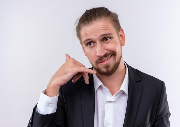 Przystojny biznesowy mężczyzna ubrany w garnitur patrząc na bok dokonywanie wezwania mnie gest stojąc na białym tle