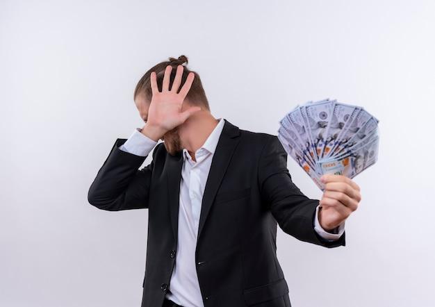 Przystojny biznesowy mężczyzna ubrany w garnitur pokazujący gotówkę czyniąc gest obrony przed pieniędzmi stojąc na białym tle