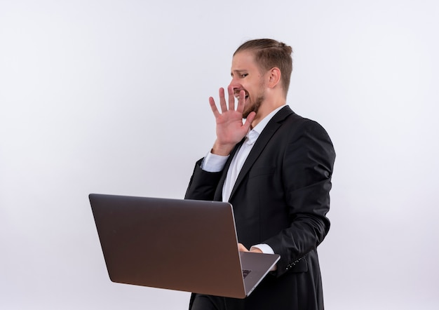 Przystojny biznesowy mężczyzna ubrany w garnitur posiadania komputera przenośnego, czyniąc gest obrony z obrzydzonym wyrazem stojącym na białym tle