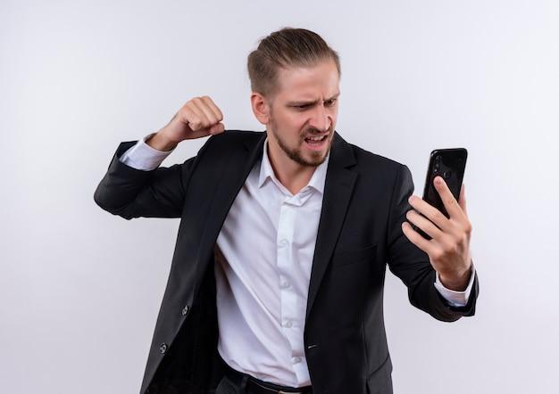 Przystojny biznesowy mężczyzna w garniturze trzymając smartfon patrząc na ekran z gniewną twarzą z zaciśniętą pięścią stojącą na białym tle