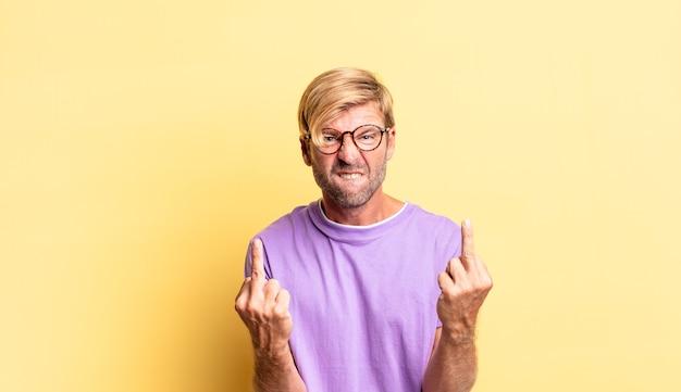 Przystojny blond dorosły mężczyzna czuje się prowokacyjny, agresywny i nieprzyzwoity, machając środkowym palcem, z buntowniczym nastawieniem
