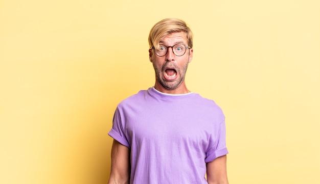 Przystojny blond dorosły mężczyzna czuje się przerażony i zszokowany, z szeroko otwartymi ustami ze zdziwienia
