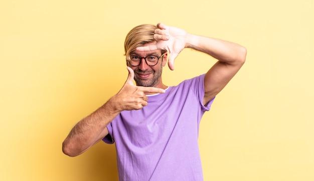 Przystojny blond dorosły mężczyzna czuje się szczęśliwy, przyjazny i pozytywny, uśmiechając się i robiąc portret lub ramkę na zdjęcia rękami