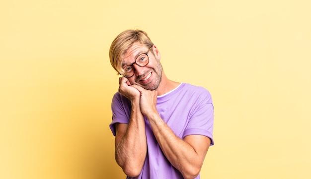 Przystojny blond dorosły mężczyzna czuje się zakochany i wygląda słodko, uroczo i szczęśliwie, uśmiechając się romantycznie z rękami przy twarzy
