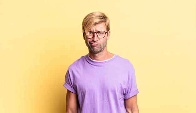 Przystojny blond dorosły mężczyzna czuje się zdezorientowany i pełen wątpliwości, zastanawia się lub próbuje wybrać lub podjąć decyzję