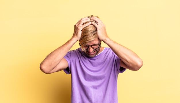 Przystojny blond dorosły mężczyzna czuje się zestresowany i sfrustrowany, podnosi ręce do głowy, czuje się zmęczony, nieszczęśliwy i ma migrenę