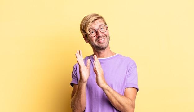 Przystojny blond dorosły mężczyzna uśmiecha się i wygląda przyjaźnie, pokazując numer pięć lub piąty z ręką do przodu, odliczając w dół