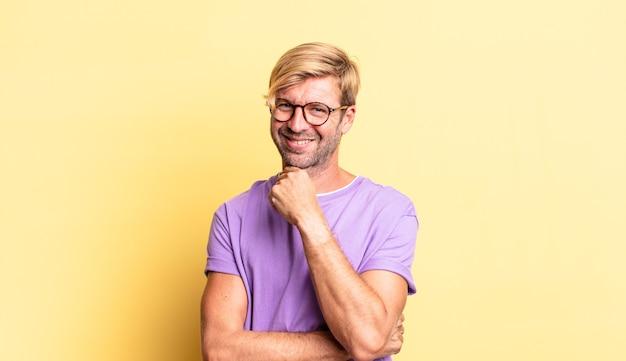 Przystojny blond dorosły mężczyzna uśmiechający się, cieszący się życiem, czujący się szczęśliwy, przyjazny, zadowolony i beztroski z ręką na brodzie