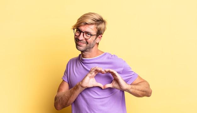 Przystojny blond dorosły mężczyzna uśmiechający się i czujący się szczęśliwy, uroczy, romantyczny i zakochany, tworząc kształt serca obiema rękami