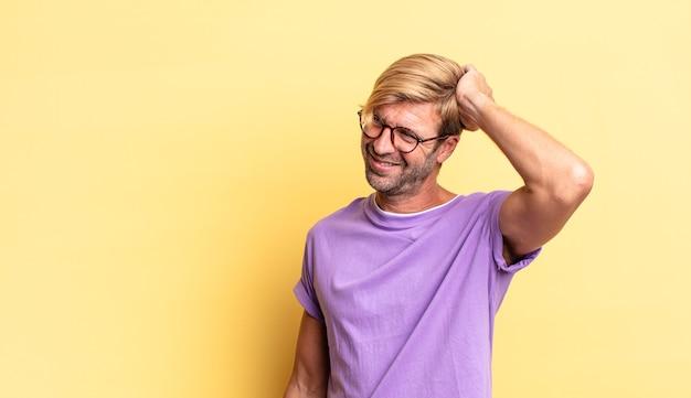 Przystojny blond dorosły mężczyzna uśmiechający się radośnie i od niechcenia, biorąc rękę w głowę z pozytywnym, szczęśliwym i pewnym siebie spojrzeniem