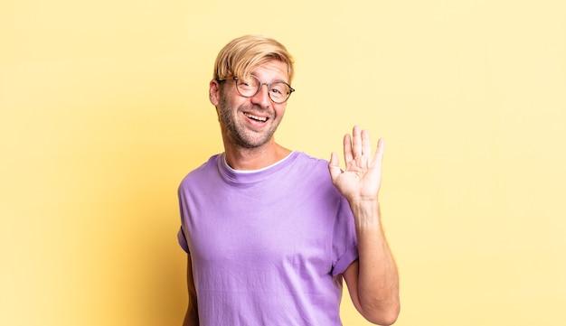 Przystojny blond dorosły mężczyzna uśmiechający się radośnie i radośnie, machający ręką, witający cię i pozdrawiający lub żegnający